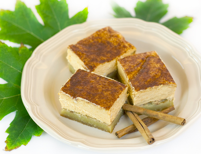 Pumpkin Cheesecake Squares pictured with three squares on a plate, cinnamon sticks and maple leaves to signify Fall