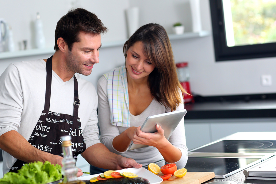 Couple cooking using a recipe on tablet