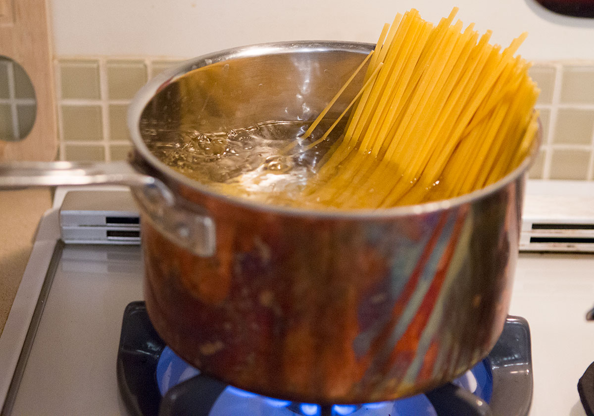 dry fettuccine noodles in a pot of boiling salted water
